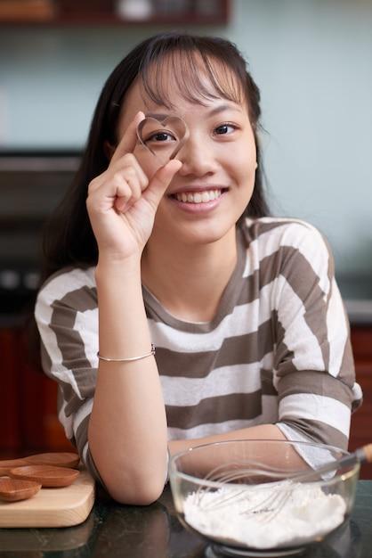 Feliz mujer asiática posando en la cocina y mirando a través del cortador de galletas en forma de oído Foto gratis