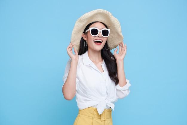Feliz mujer asiática en ropa casual de verano aislada sobre fondo azul. Foto Premium