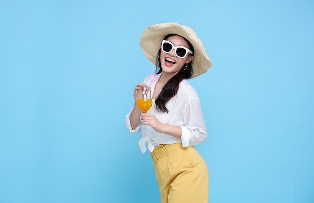 Feliz mujer asiática en ropa casual de verano con vaso de jugo de fruta fresca bebida aislado sobre fondo azul. Foto Premium