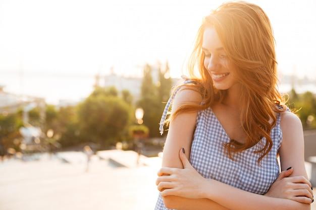 Feliz mujer bonita de pie con los brazos cruzados y riendo Foto gratis