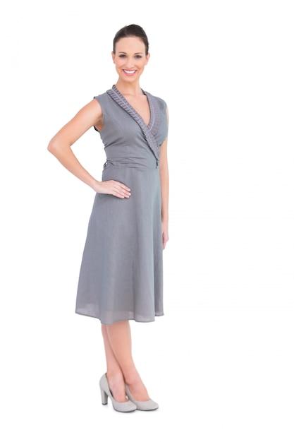 399fa820f Feliz mujer elegante en elegante vestido posando mano en la cintura ...