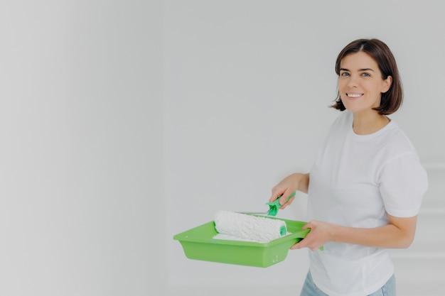 Feliz mujer encantadora en camiseta casual blanca, posa con rodillo de pintura y bandeja especial Foto Premium