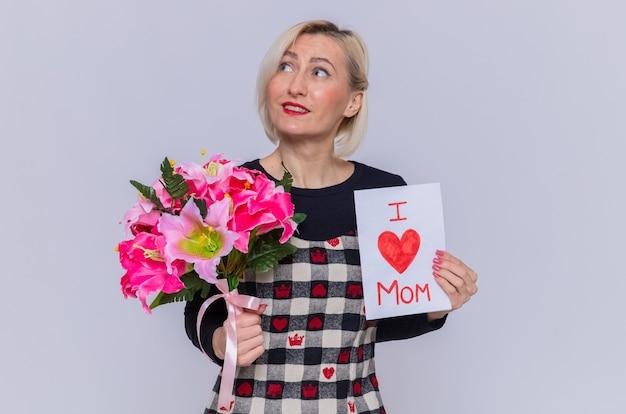 Feliz mujer joven en un hermoso vestido con tarjeta de felicitación y ramo de flores mirando hacia arriba sonriendo alegremente celebrando el día de la madre de pie sobre la pared blanca Foto gratis