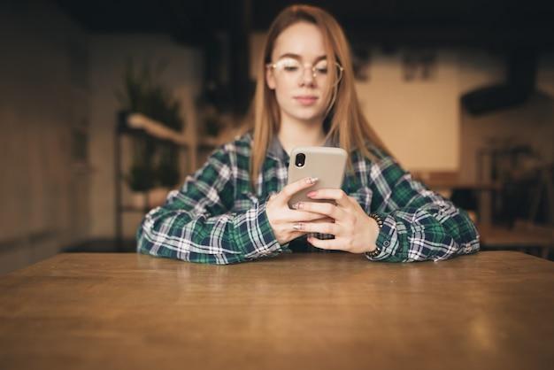 Feliz mujer joven sentada en la cafetería enviando mensajes de texto en su teléfono inteligente Foto Premium