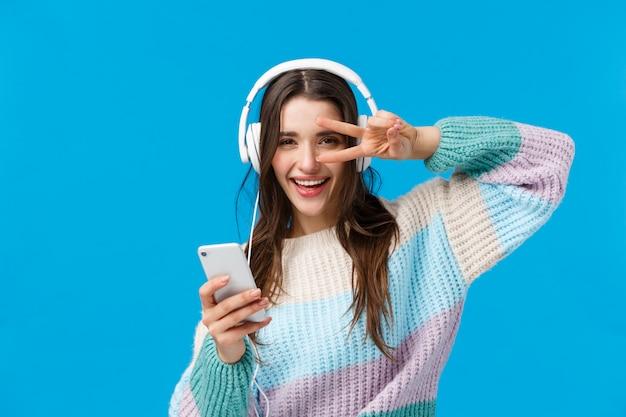 Feliz mujer morena guapa descarada en auriculares, suéter de invierno, disfrutando de sus canciones favoritas en nuevos auriculares, muestra paz, gesto de disco con teléfono inteligente, sonriendo cámara contenta Foto Premium