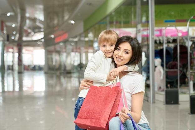 Feliz mujer y niña en posando, sonriendo en el centro comercial. Foto gratis