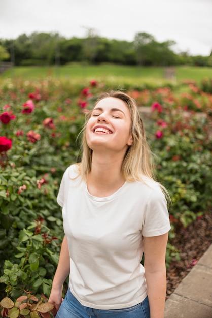 c64cf53ac Feliz mujer de pie en el jardín de flores | Descargar Fotos gratis