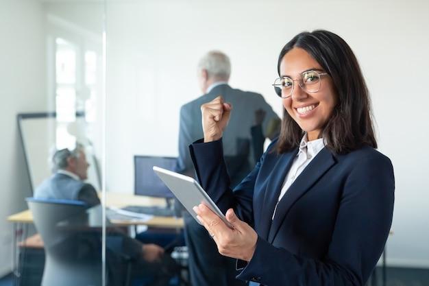Feliz mujer profesional en gafas y traje sosteniendo tableta y haciendo gesto de ganador mientras dos hombres de negocios trabajan detrás de una pared de vidrio. copie el espacio. concepto de comunicación Foto gratis