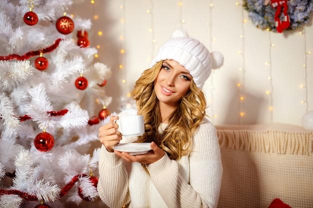 Feliz mujer rubia bebiendo café, habitación interior con decoración navideña Foto Premium