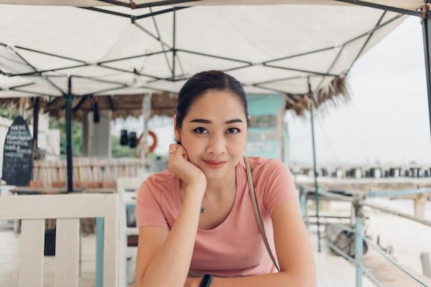Feliz mujer está sentada en el restaurante en la playa. Foto Premium
