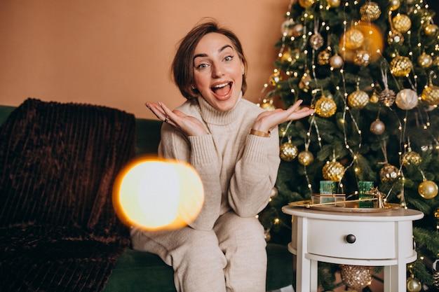 Feliz mujer sentada en el sofá junto al árbol de navidad Foto gratis