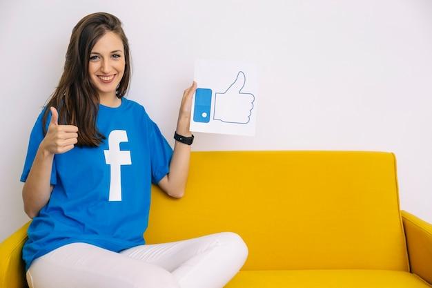 Feliz mujer sentada en el sofá sosteniendo como icono mostrando el pulgar en señal Foto gratis