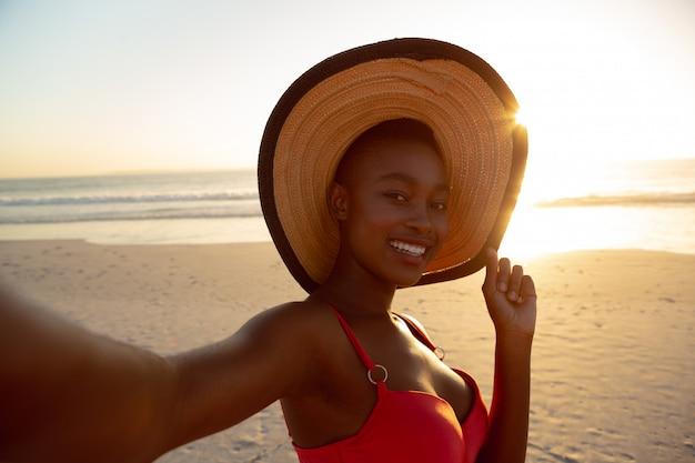 Feliz mujer con sombrero de pie en la playa Foto gratis