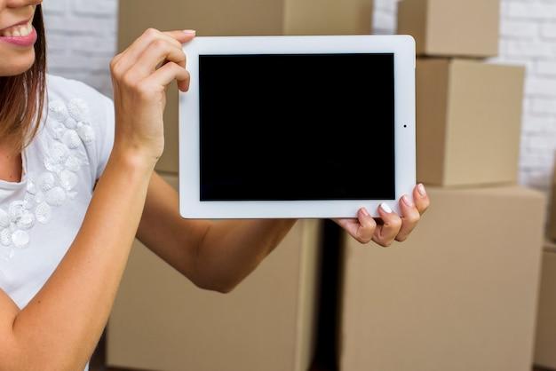 Feliz mujer sosteniendo una maqueta de tableta Foto gratis