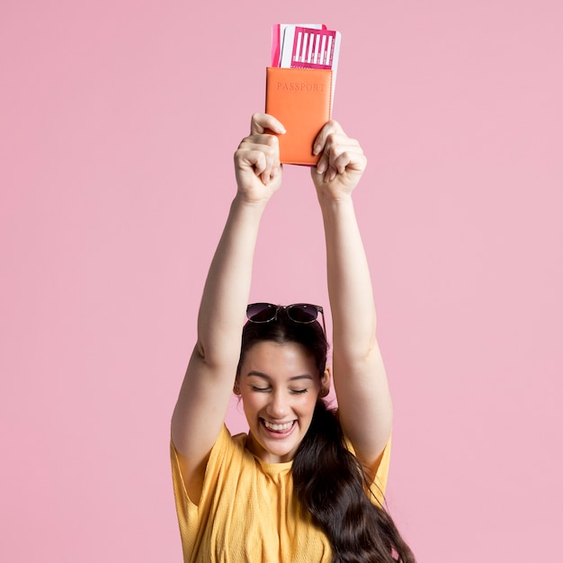 Feliz mujer sosteniendo su pasaporte Foto gratis