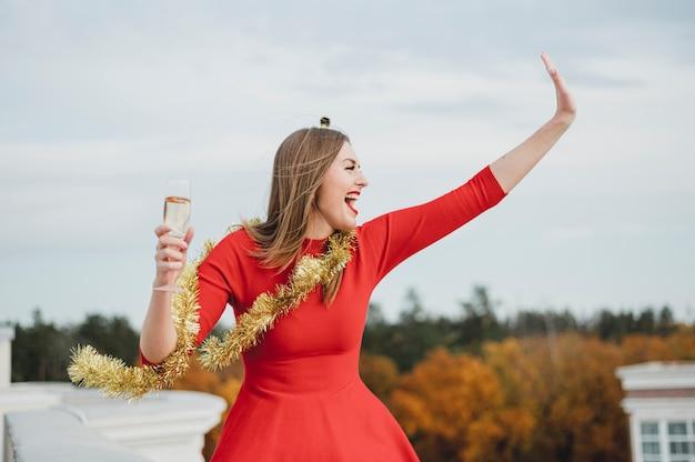 Feliz mujer en vestido rojo de fiesta en la azotea Foto gratis