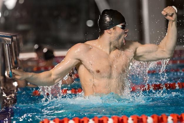 Feliz nadador masculino con bloque inicial Foto gratis
