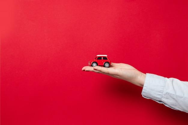Feliz navidad y felices fiestas tarjeta de felicitación o banner web. mano femenina con una camisa azul sostiene un modelo de automóvil rojo sobre un rojo oscuro con espacio de copia Foto Premium