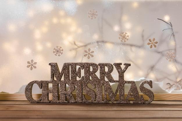 Feliz navidad letrero en mesa de madera cerca de banco de nieve, copos de nieve y luces Foto gratis