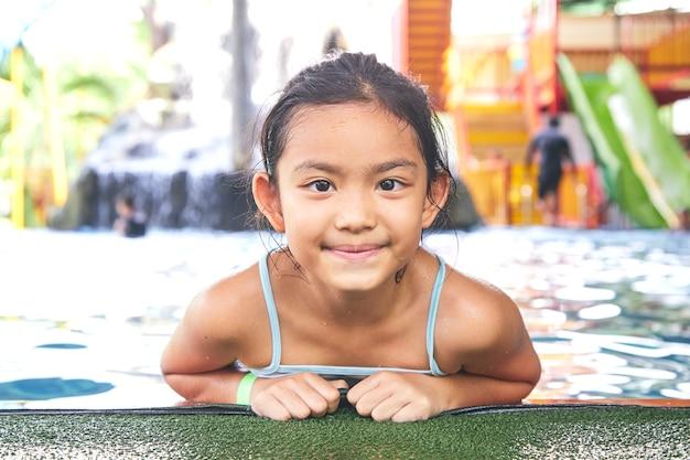 Feliz niña asiática en la piscina Foto Premium