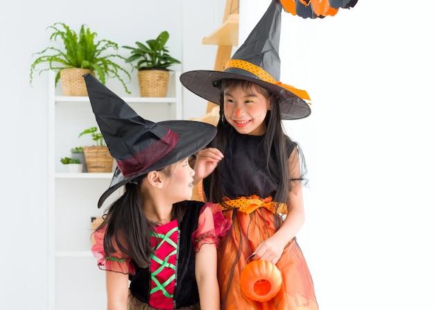 Feliz niña asiática en traje de bruja en la celebración de halloween. Foto Premium