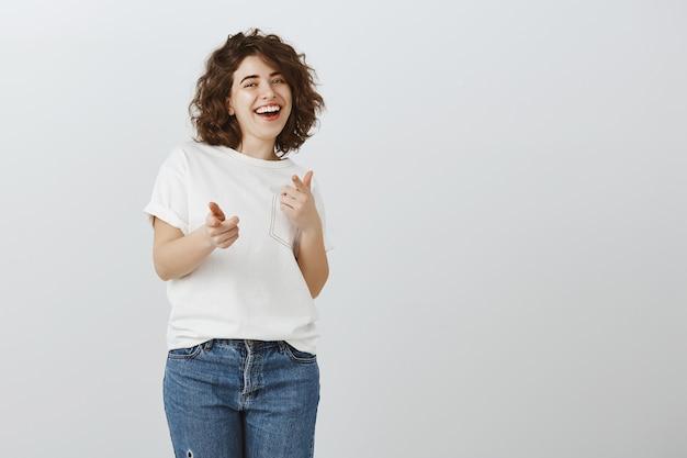 Feliz niña bonita señalando con el dedo, bien hecho, buen trabajo, buen trabajo, gesto de felicitaciones Foto gratis