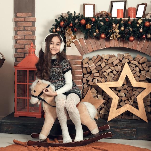Feliz niña morena con el pelo largo sentado en un caballo de juguete en navidad decorado habitación. Foto Premium