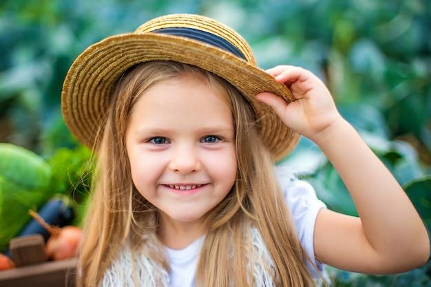Feliz niña con sombrero de paja en campo de repollo Foto Premium