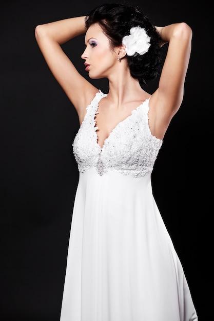 Feliz novia hermosa sexy mujer morena en vestido de novia blanco y maquillaje brillante Foto gratis