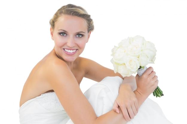 7ff76a4223a39 Feliz novia rubia sentada en el suelo mientras sostiene un ramo ...