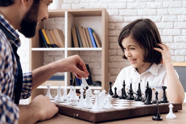 Feliz padre barbudo juega al ajedrez con su hijo adolescente. Foto Premium