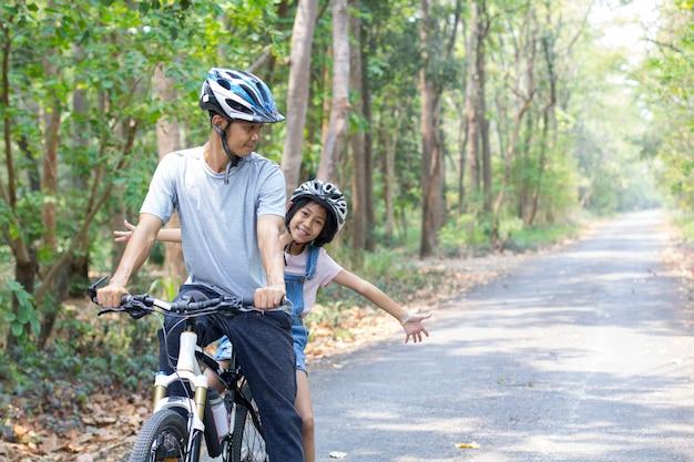 Feliz padre e hija en bicicleta en el parque Foto Premium