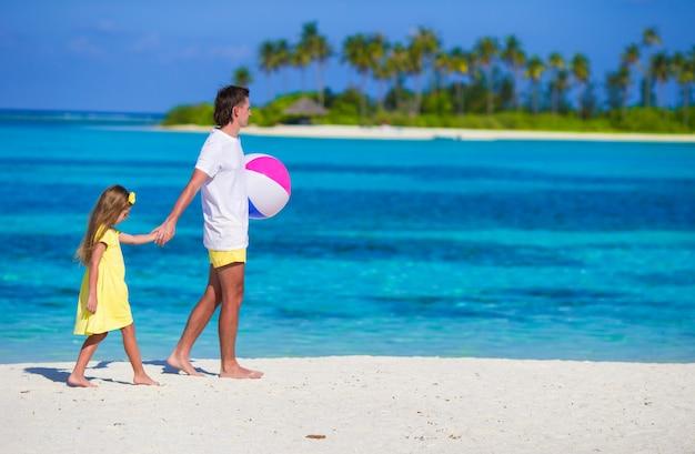 Feliz padre e hija jugando con pelota al aire libre en la playa Foto Premium