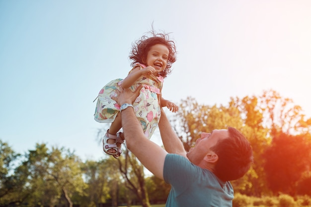 Feliz padre e hija riendo juntos al aire libre Foto gratis