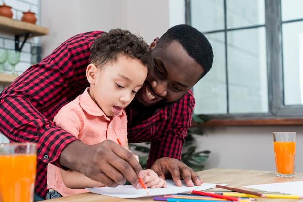 Feliz padre e hijo negros dibujando en la mesa Foto gratis