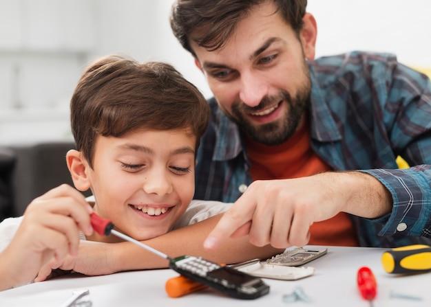 Feliz padre e hijo reparando un teléfono Foto gratis