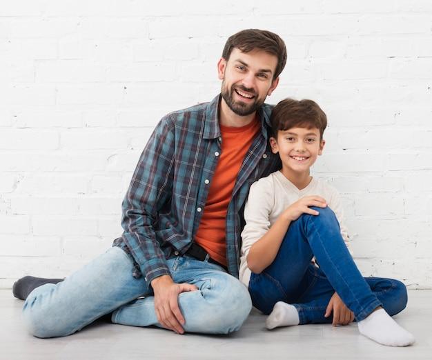 Feliz padre e hijo sentados en el piso Foto gratis