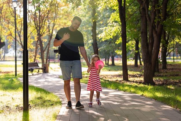 Feliz padre y niña caminando sosteniendo en la mano en el parque de verano Foto Premium