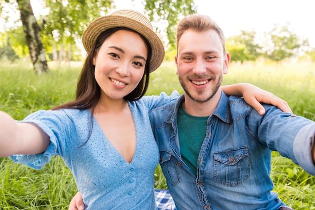 Feliz pareja adulta multirracial tomando selfie en el parque Foto gratis