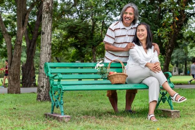 Feliz pareja de ancianos asiáticos con cesta de frutas en el parque. Foto Premium