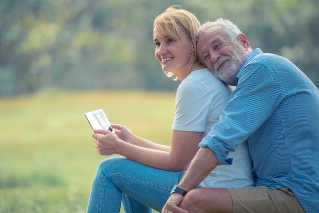 Feliz pareja de ancianos disfrutando de pasar tiempo juntos, abrazándose, hablando con la cara sonriente y riendo Foto Premium