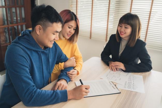 Feliz pareja asiática joven y agente de bienes raíces Foto gratis
