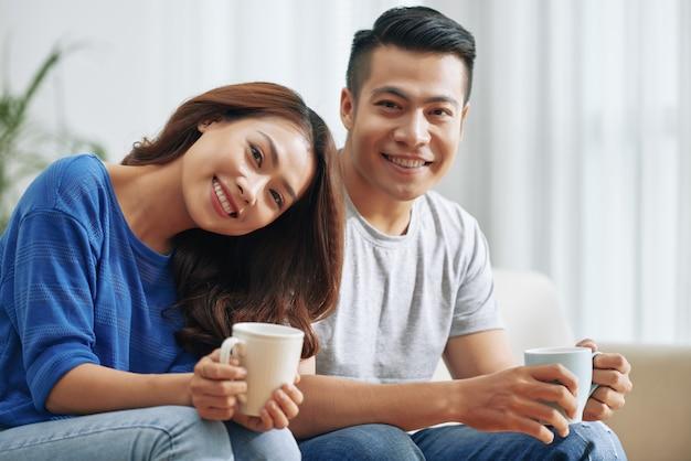 Feliz pareja asiática sentada en el sofá en casa con tazas de té y sonriendo Foto gratis
