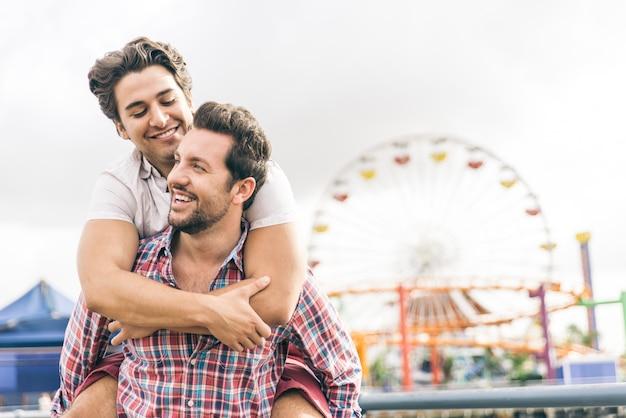 Feliz pareja de enamorados jugando en la playa Foto Premium