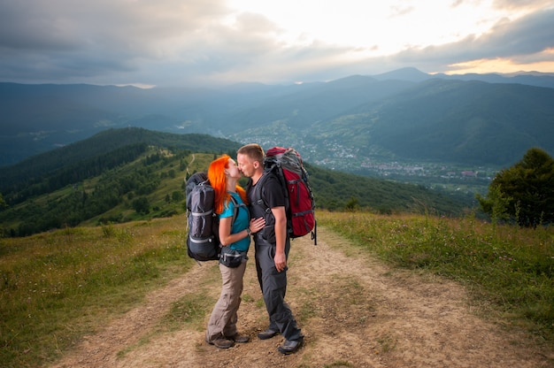 Feliz pareja excursionistas se besa en el camino en las montañas. Foto Premium