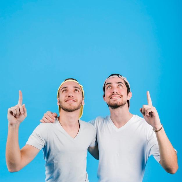 Feliz pareja gay abrazando y apuntando hacia arriba Foto gratis