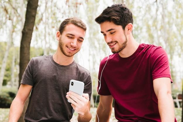 Feliz pareja gay en auriculares escuchando música en el móvil en el parque Foto gratis