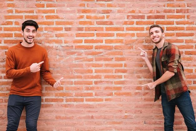 Feliz pareja gay de pie junto a la pared de ladrillo y apuntando con los dedos Foto gratis