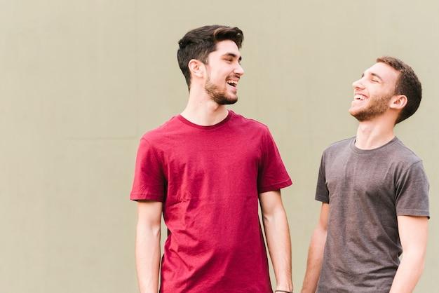 Feliz pareja gay de pie y riendo Foto gratis