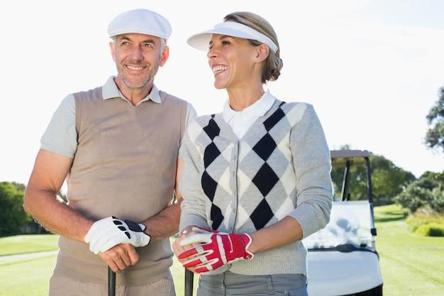Feliz pareja de golf con buggy de golf detrás Foto Premium